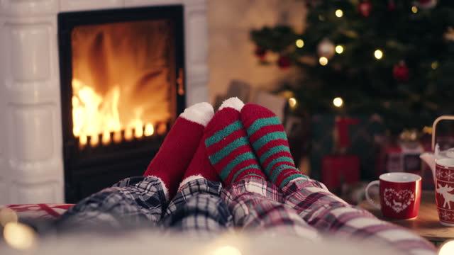 parfötter i mysiga julullstrumpor nära öppen spis med dekorerat xmasträd och tee cup i bakgrund - strumpa bildbanksvideor och videomaterial från bakom kulisserna
