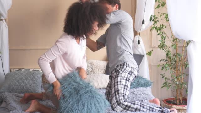 vídeos y material grabado en eventos de stock de pareja lucha con almohadas en la cama - almohada