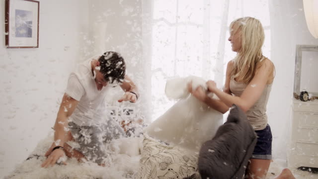 Couple fighting with pillows in bedroom video