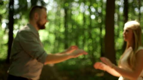 vídeos y material grabado en eventos de stock de plano medio dolly shot tilt up par coquetear en día soleado en bosque - miembro humano
