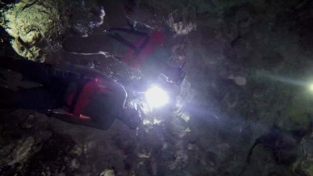 LOW ANGLE VIEW: Couple freediving among rock formations in Grand Cenote sinkhole video