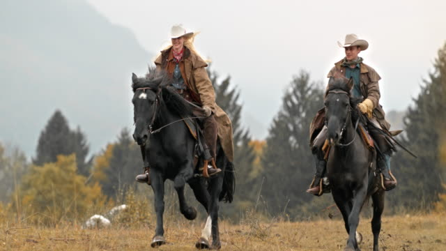 SLO MO DS Couple galloping on their horses across meadow video