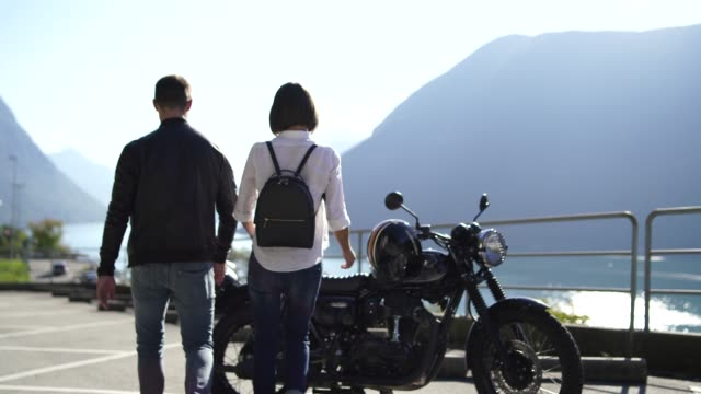 Couple getting on a motorcycle next to a lake on a sunny day Details of people enjoying a lakeside on a sunny day crash helmet stock videos & royalty-free footage