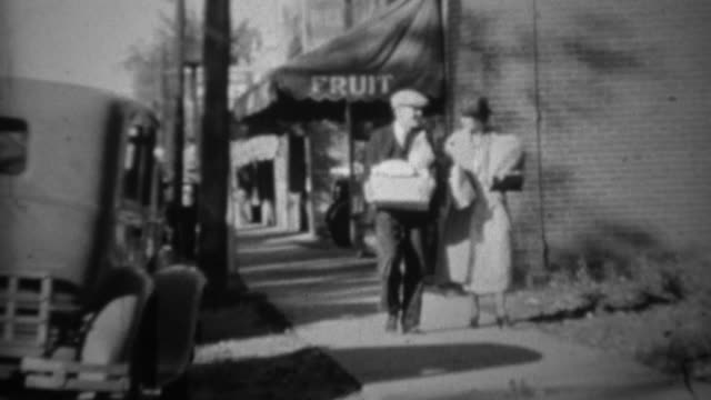 1936: Couple grocery shopping from fruit store walking bags of food.