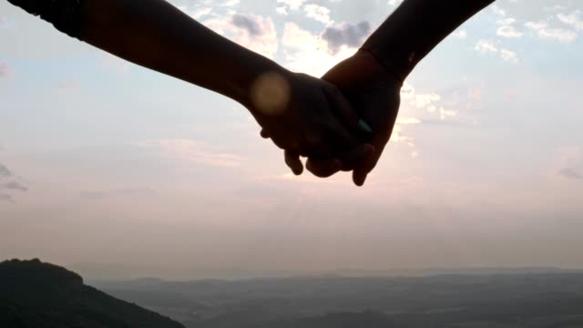 A couple hand-holding and walking towards the sunset, Slow motion, close up