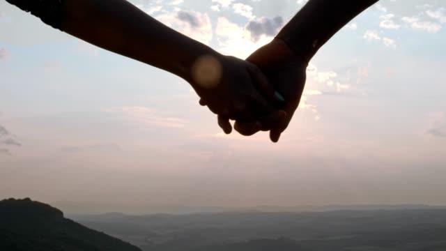 a couple hand-holding and walking towards the sunset, slow motion, close up - ręka człowieka filmów i materiałów b-roll