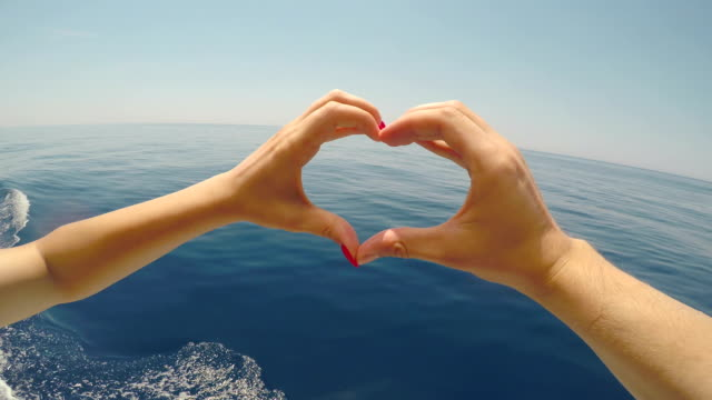 couple hands touching fingers forming a heart shape with beautiful blue sea and summer sky in background - mano donna dita unite video stock e b–roll