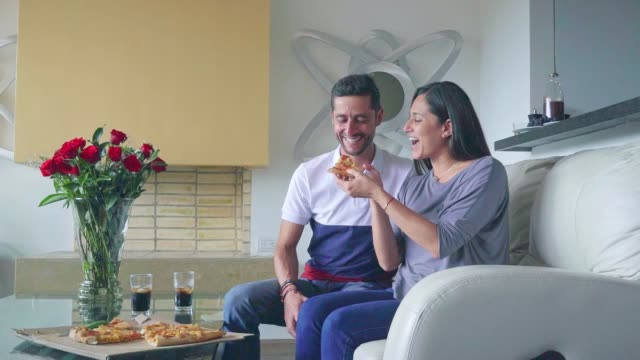 Couple has fun while eating pizza