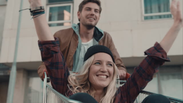 Couple haveing fun with shopping cart Selected Takes - Shot on RED Epic woman pushing cart stock videos & royalty-free footage