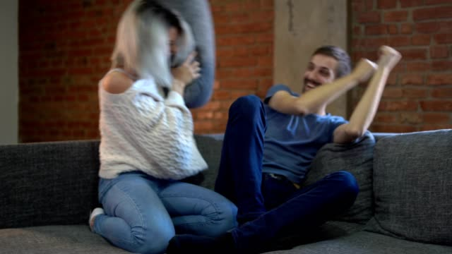 a couple having a pillow fight at home - miroslav mitic stock videos and b-roll footage