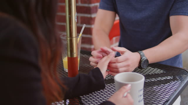 a couple having a thumb war at an outdoor table - wrestling stock videos and b-roll footage