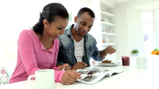 Couple Having Breakfast And Reading Magazine In Kitchen video