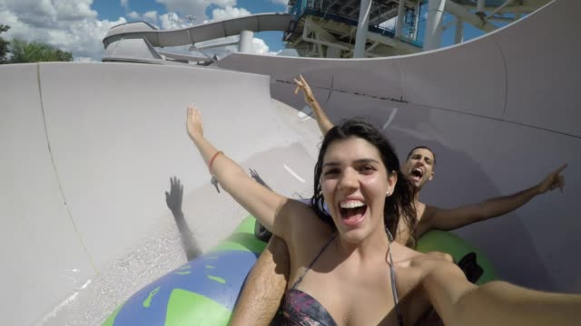 Couple having fun and sliding down in a water slide video