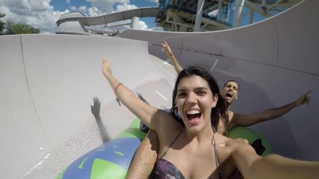 Pareja diversión y deslizarse en un tobogán de agua - vídeo