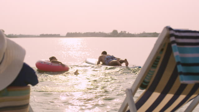 stockvideo's en b-roll-footage met slo mo paar plezier in het meer bij zonsondergang - opblaasband