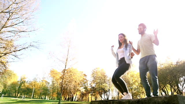 Couple having fun listening to music on headphones and dancing video