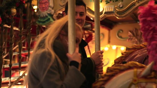 paar hat spaß am karussell - weihnachtsmarkt stock-videos und b-roll-filmmaterial