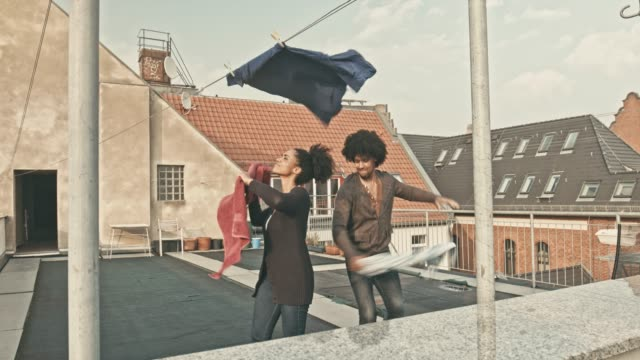 Couple having fun putting the laundry to dry at terrace Real time video of black couple having fun in the terrace putting the laundry to dry, they both are very playful with the towels. hanging stock videos & royalty-free footage