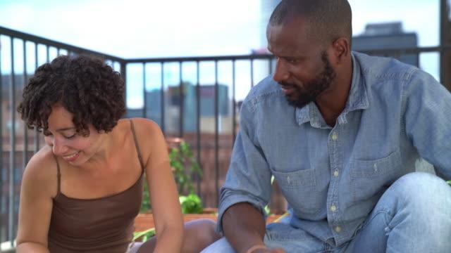 Couple having fun tending to their urban garden video