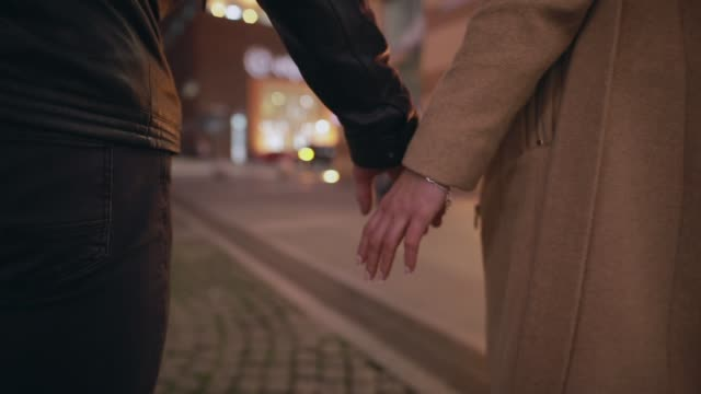 Couple held hands and walks away in the night city video