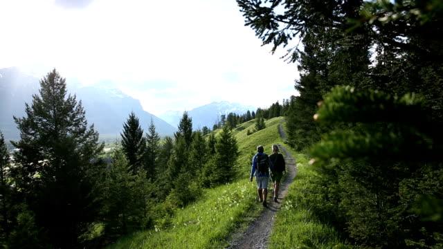 stockvideo's en b-roll-footage met couple hike along trail across mountain ridge - ridderlijkheid
