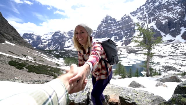Couple hiking in the heart of the Canadian rockies, man pulls out hand to assist female on mountain top