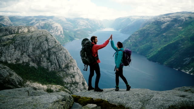 couple  hiking near preikstolen and giving high five at lysefjorden - parco nazionale video stock e b–roll