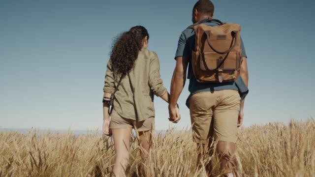 par vandring genom torrt gräs på ett berg - pojkvän bildbanksvideor och videomaterial från bakom kulisserna