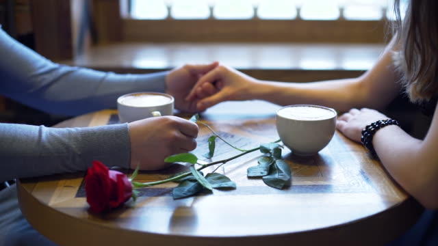 Couple Holding by Hands in Coffee Shop Close Up of Couple Dating in a Coffee Shop. They Holding by Hands and Enjoying Time Together. Slow Motion. Love, Romance, Dating, Celebrating Valentine Day Concept valentines day stock videos & royalty-free footage