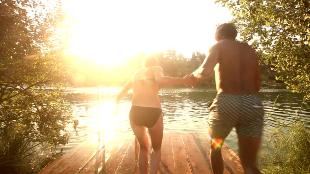 Couple holding hands and jumping into water from river dock video