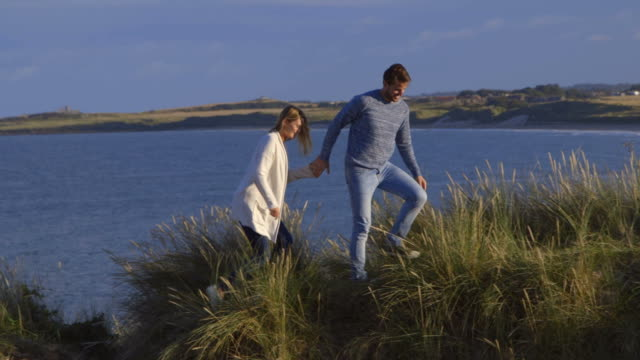Couple holding hands and walking through sand dunes in slow motion video