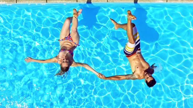 SLO MO CS Couple holding hands falling into pool backwards Slow motion medium crane shot of a man and a woman holding hands and falling into the pool backwards with a smile on their faces. tripping falling stock videos & royalty-free footage