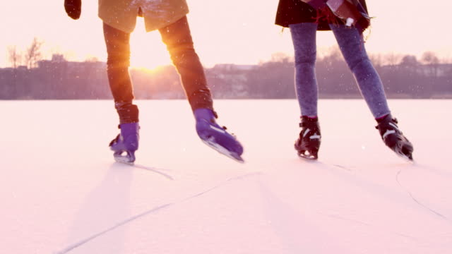 4K Couple holding hands ice skating on sunny frozen lake, real time