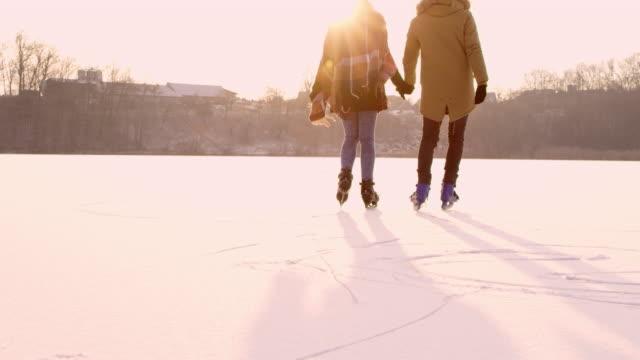 4 k par hålla händerna skridskoåkning på soliga frusen sjö, slow motion - vintersport bildbanksvideor och videomaterial från bakom kulisserna