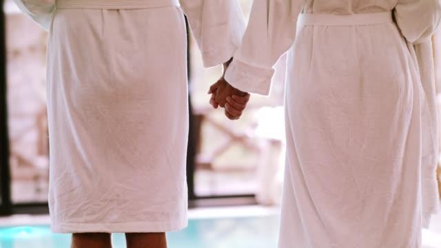 vidéos et rushes de couple, main dans la main à côté de la piscine - peignoir