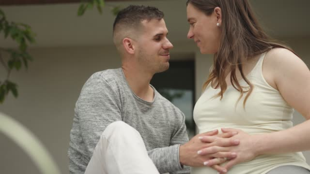 Couple holding hands on pregnant womans belly