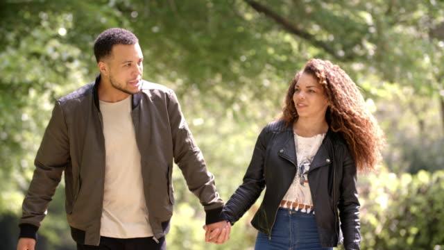 田園環境の中を歩いて、手を繋いでいるカップル フロント ビュー - 対面点の映像素材/bロール