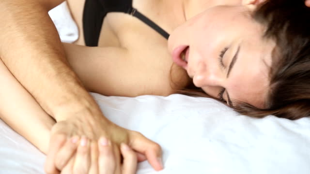 couple holding hands while having passionate hot sex on bed - seduzione video stock e b–roll