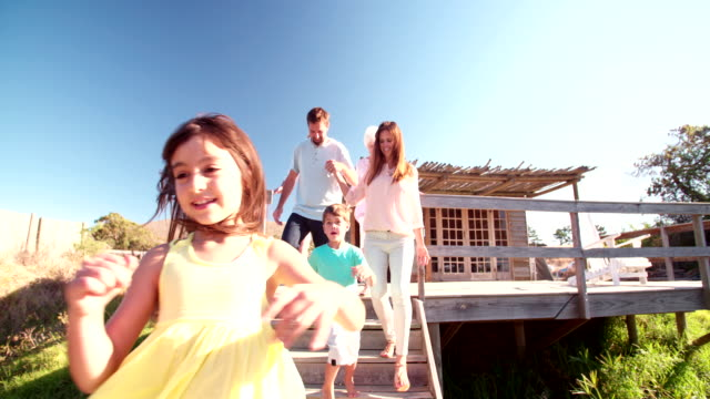 Couple holding hands while their children run on a jetty video