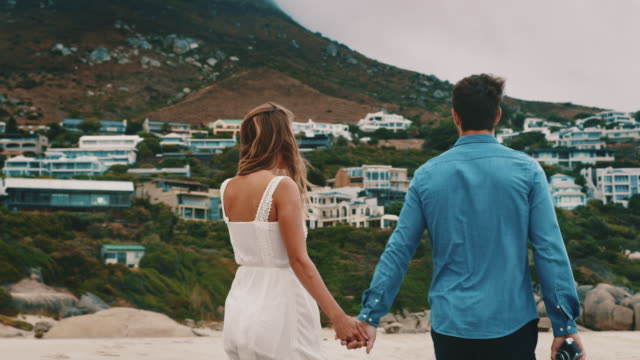 Couple holding hands while walking at sea shore