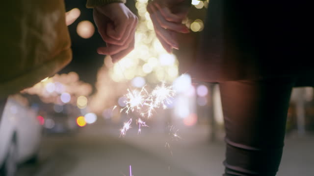 WS Couple holding sparklers while walking in the city at Christmas time Wide rear view shot of a young couple holding sparklers while walking down city street decorated with Christmas lights at night. holiday stock videos & royalty-free footage