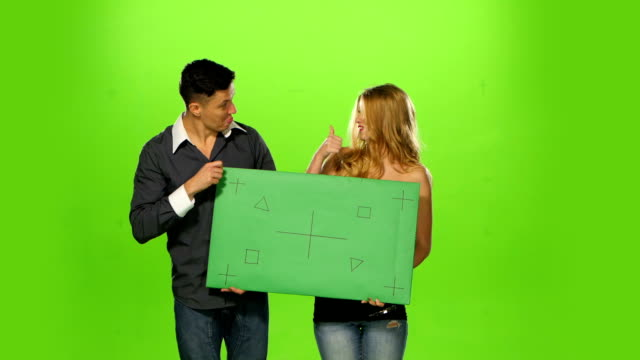 Couple holding up a blank sign, green screen video