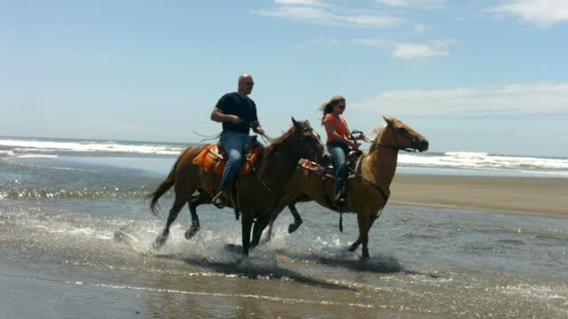 Couple horseback riding on beach, slow motion video