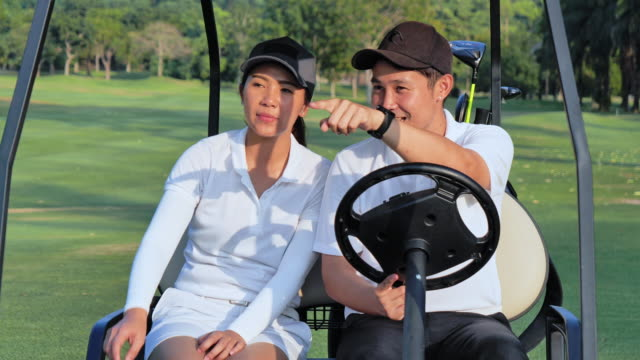 Couple in a golf cart at the golf course.