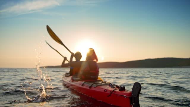 vídeos de stock, filmes e b-roll de slo mo par em um caiaque de mar vermelho, passando sobre a água no sol - remo esporte aquático