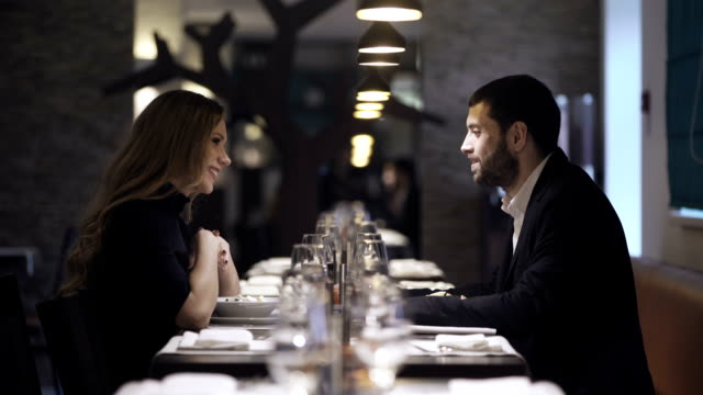 Couple in a restaurant Couple in a restaurant is talking and smiling formalwear stock videos & royalty-free footage