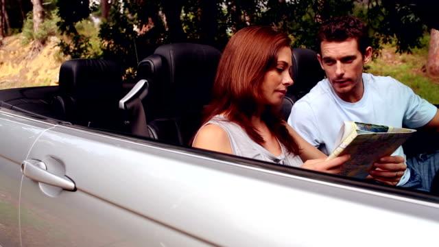 stockvideo's en b-roll-footage met couple in a silver car - roadmap