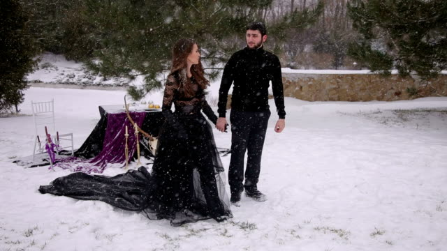 Couple in black clothes under heavy snow. Wedding. video