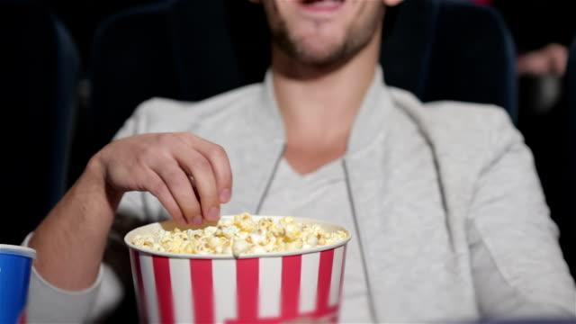 stockvideo's en b-roll-footage met paar in cinema theater lettend op een film - popcorn