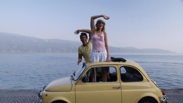vidéos et rushes de couple dans une voiture classique - inclinaison vers le haut